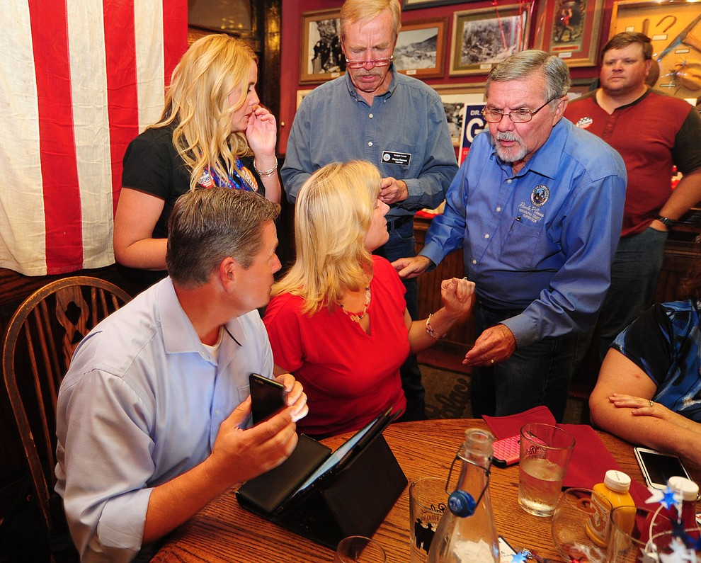 Yavapai County Supervisor Jack Smith shows fellow supervisor Rowle Simmons the initial results while Tom Thurman and supporters look on as Republicans gathered at The Palace Restaurant and Saloon for primary election results Tuesday, August 30, 2016. (Les Stukenberg/The Daily Courier)