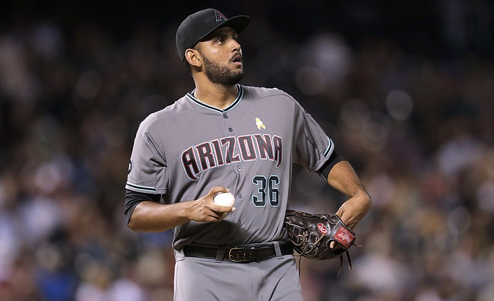 Arizona Diamondbacks relief pitcher Enrique Burgos reacts after throwing a wild pitch to allow Colorado Rockies' DJ LeMahieu to score from third base in the eighth inning of a baseball game Friday, Sept. 2, 2016, in Denver. The Rockies won 14-7.
