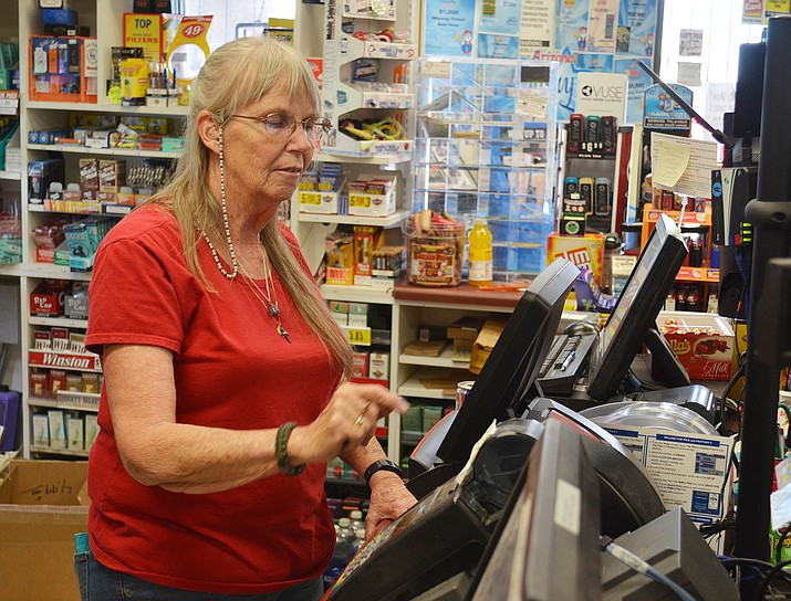 Gas Plus Assistant Manager Jeanne Montez rings up lottery tickets for customers.