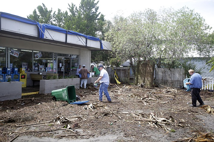 Workers clean up debris, caused by Hurricane Hermine, in the parking lot in front of convenience store, Friday, Sept. 2, 2016, in Cedar Key, Fla. Hermine was downgraded to a tropical storm after it made landfall.