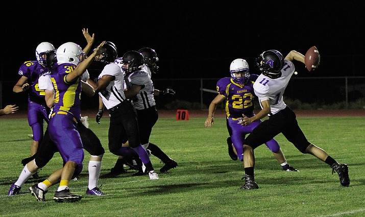 Kingman Academy's Kekoa Makaiwi-Stroup gets off a pass before Kingman's Darrell Mitchell (22) and Josh Baker (30) can get to him in the second quarter of Academy's 48-0 win Friday at KHS. Makaiwi-Stroup passed for 193 yards and two touchdowns for the Tigers.