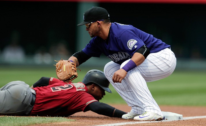 Colorado Rockies first baseman Gerardo Parra fields the pickoff throw as Arizona Diamondbacks' Jean Segura dives back to first in the first inning Sunday, Sept. 4, in Denver.