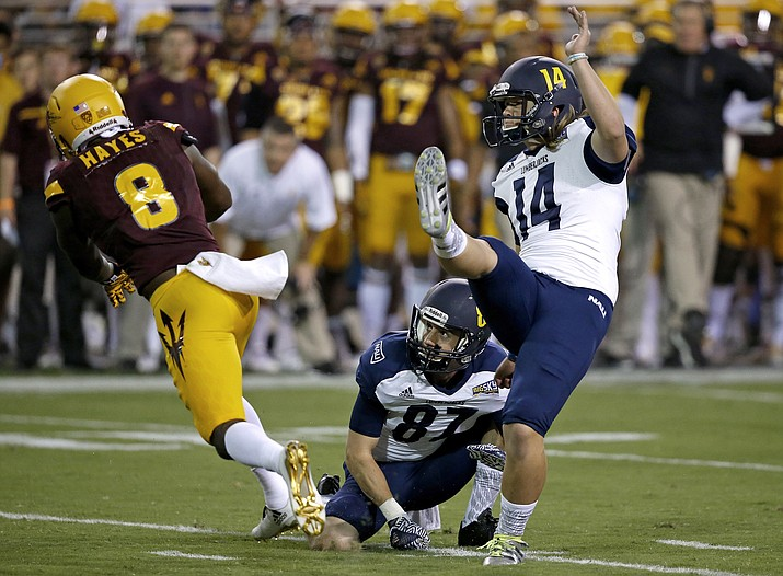Northern Arizona's Griffin Roehler (14) kicks a field goal with the help of holder Hunter Burton (87) as Arizona State's De'Chavon Hayes (8) arrives late with pressure during the first half of an NCAA college football game Saturday, Sept. 3, 2016, in Tempe, Ariz.