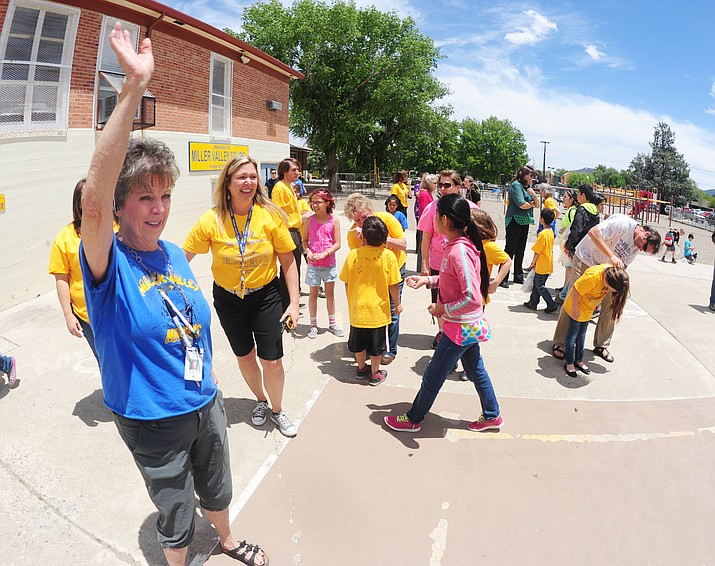 Staff wave and say goodbye to students on the last day of school at Miller Valley School in Prescott in May 2015.