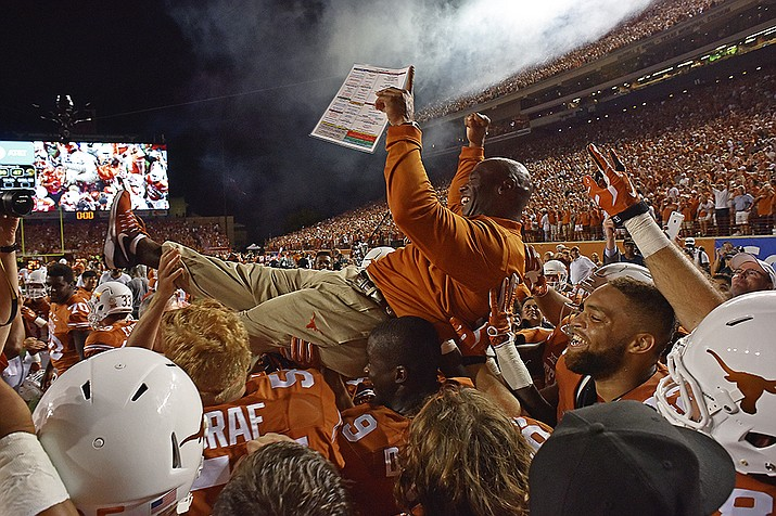 In this Sept. 4, 2016, file photo, Texas head coach Charlie Strong is carried by players after defeating Notre Dame in double overtime of an NCAA college football game, in Austin, Texas. Texas is ranked for the first time under coach Charlie Strong, coming in at No. 11 in the latest Associated Press college football rankings after a rousing opening victory against Notre Dame.