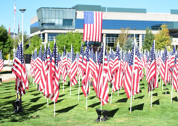 Volunteers at the Prescott Valley Civic Center place the 3000 flags Friday morning honoring the 3000 victims in the September 11, 2001 terrorist attacks,  as part of a Healing Field. (Les Stukenberg/The Daily Courier)