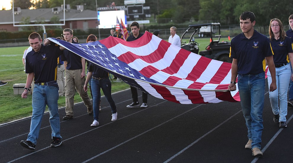 Prescott High's AFJROTC present the colors before the Badgers take on Cactus Shadows Friday night in Prescott. (Les Stukenberg/The Daily Courier)