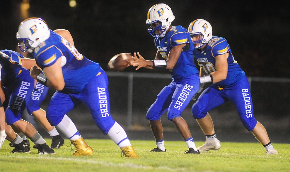 Prescott's Dawson Winslow takes the snap as the Badgers take on Cactus Shadows Friday night in Prescott. (Les Stukenberg/The Daily Courier)