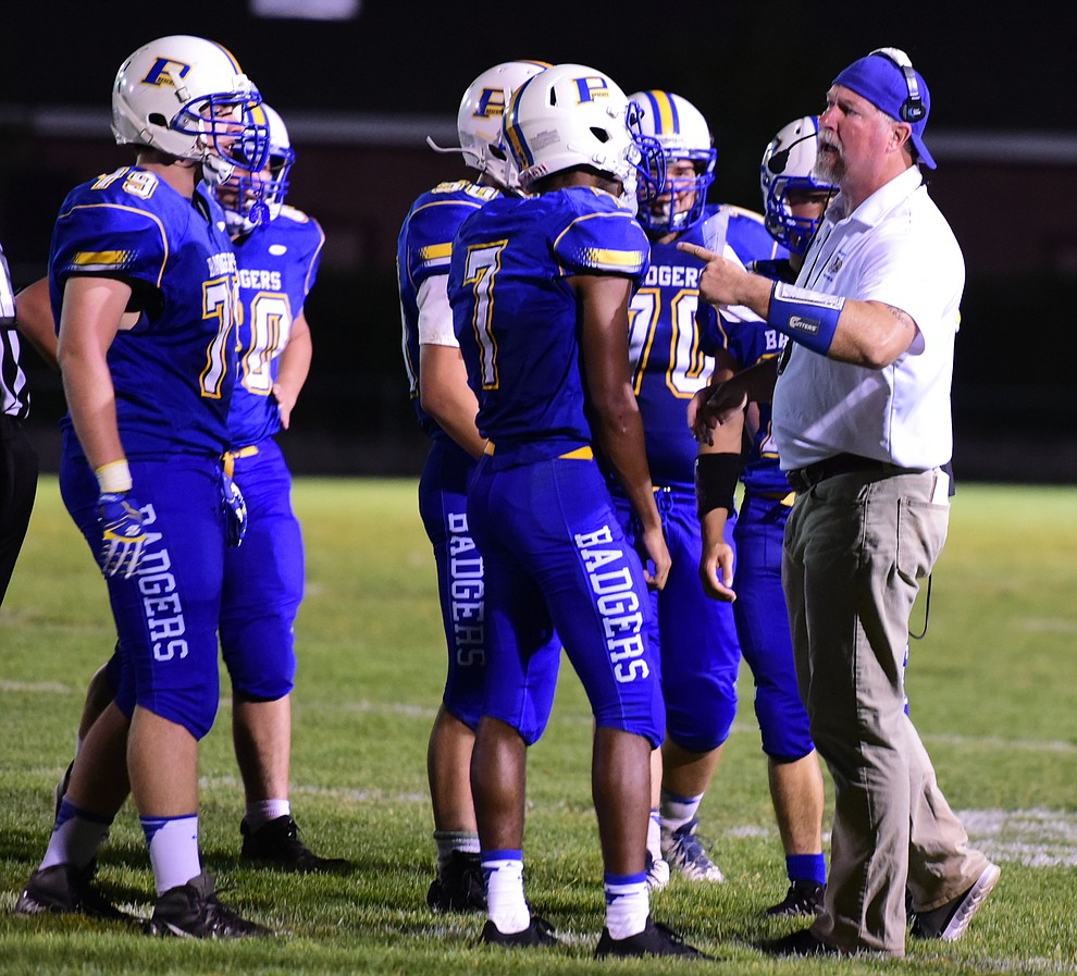 Prescott's Head Coach Michael Gilpin talks to his players as the Badgers take on Cactus Shadows Friday night in Prescott. (Les Stukenberg/The Daily Courier)