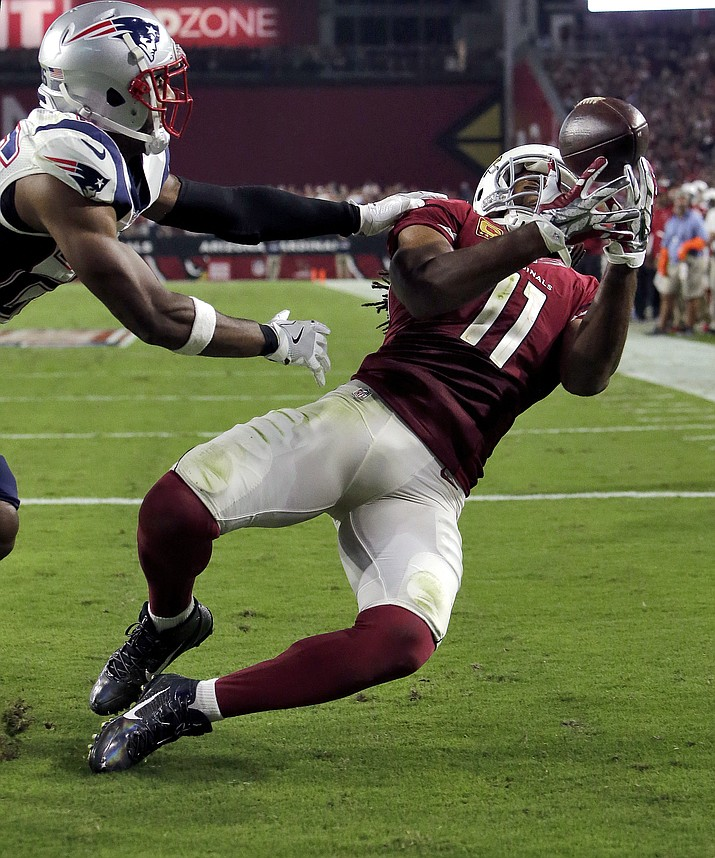 Arizona Cardinals wide receiver Larry Fitzgerald (11) catches his 100th career  touchdown pass during the second half of an NFL football game as New England Patriots cornerback Logan Ryan (26) defends, Sunday, Sept. 11, in Glendale.