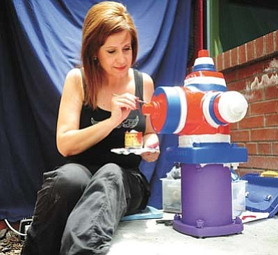 Jenn Winters (Ashcraft) puts the finishing touches on a fire hydrant tribute to the Granite Mountain Hotshots in 2015. Winters was in New York City and witnessed the planes flying into the World Trade Center Towers. She got caught in the crush of humanity running from the towers.