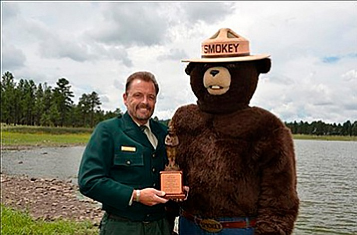 Fire prevention specialist Bob Blasi accepts his award from Smokey Bear.