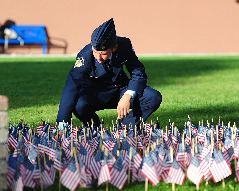 Prescott High School AFJROTC cadet Tobias Buettner straightens some of the flags represetning those lost in the 9/11 terrorist attacks before a 9/11 Remembrance ceremony Monday morning at Prescott High School.  (Les Stukenberg/The Daily Courier)