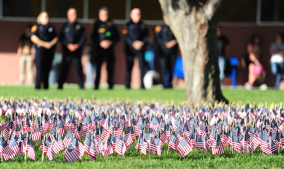 Flags representing the victims of the September 11, 2001 terrorist attacks flutter in the breeze during a 9/11 Remembrance ceremony Monday morning at Prescott High School.  (Les Stukenberg/The Daily Courier)