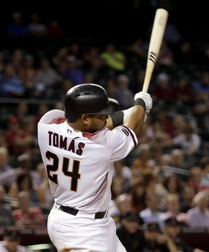 Diamondbacks Yasmany Tomas follows through on his grand slam home run against the Colorado Rockies during the sixth inning Monday, Sept. 12.