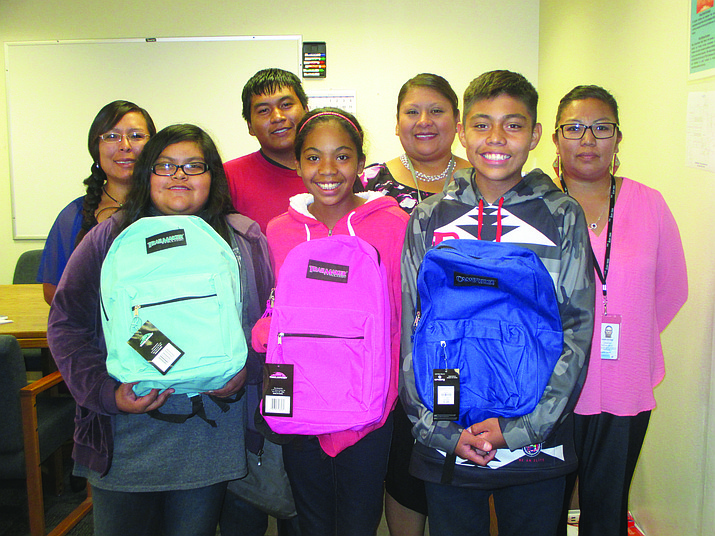 Hopi Junior High students were glad to display handbags brought by the vice chairman's office that was donated by MILK. They are, from left, Anna Saufkie, executive secretary from the vice chairman's office; Elise Sakenima, Jarius Campus, Aiyana Tikas, head teacher Lucille Sidney, Xander Mitchell and Dawn Keevama, receptionist for the vice chairman's office. Photo/Stan Bindell