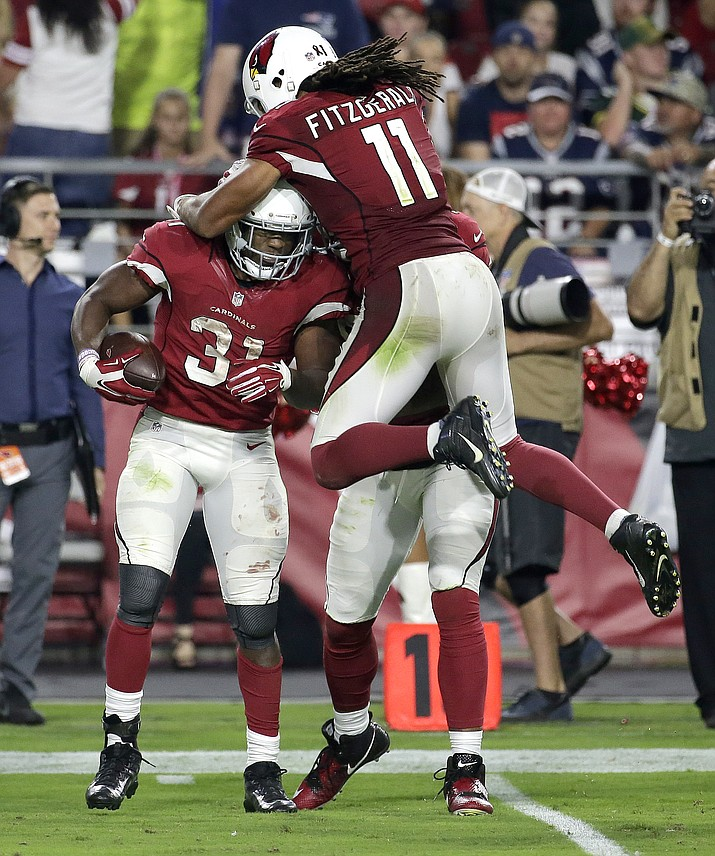 Arizona Cardinals running back David Johnson (31) celebrates his first down run with teammate Larry Fitzgerald during the second half Sunday against the New England Patriots in Glendale.