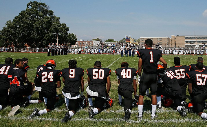 Woodrow Wilson High's Edwin Lopez (1) stands while some of his teammates kneel during the national anthem Sept. 10 before Woodrow Wilson High School played Highland High School in Camden, N.J.
