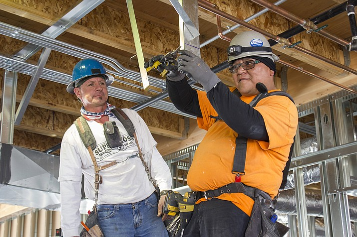 Men work on the Mohave Community College Student Services Center earlier this year.