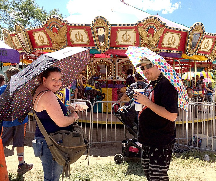 Jennifer and Daniel Lewis enjoy the sunny weather and a hotdog at Saturday's Yavapai County Fair while they wait for their daughters, Rachel and Cheyenne, riding the Merry-Go-Round. Rachel, 10, joined 4-H this year and her rabbit won the Reserve Champion ribbon.