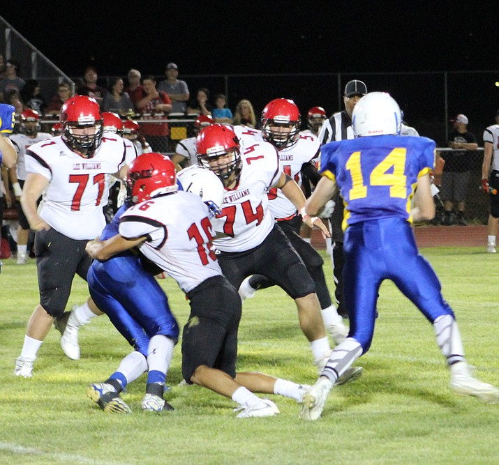 Lee Williams linebacker Andrew Davis wraps his arms around Kingman ball carrier Miguel Salinas with Phillip Rebai (71), Mike Bathauer (74) and Matt Shaw (54) coming in to help Aug. 26 at KHS. The Vols need to stop Mingus' rushing attack at 7 p.m. today at LWHS.