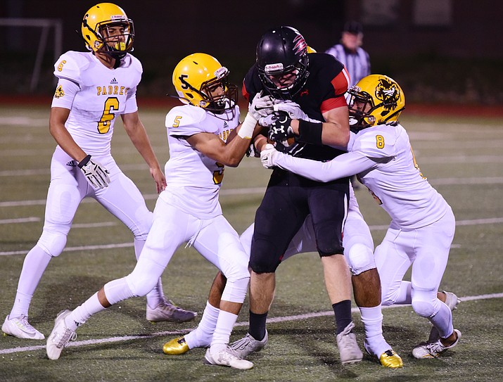 Bradshaw Mountain's Timmy Young gets tackled by a host of Padres after a long gain as the Bears take on the Marco de Niza Padres Friday night in Prescott Valley. (Les Stukenberg/The Daily Courier)