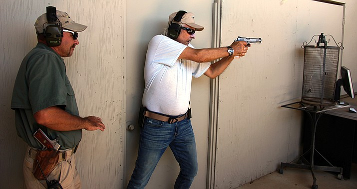 Eberhard Wensauer (right) makes his way through an indoor pistol range simulation under the supervision of Gunsite Academy instructor Gary Smith.