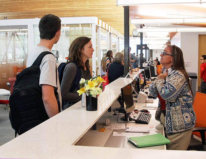 Jane Watts assists two students, Kati Shackelford and Trayson Rubio, inside the new Student Services Center Friday.