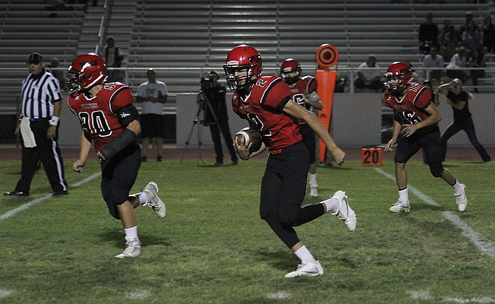 Andrew Herrera runs back an interception for 25 yards with Kael Juelfs (90) leading the way for a touchdown Friday.