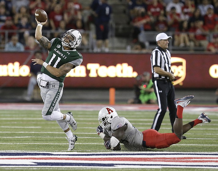 Hawaii quarterback Ikaika Woolsey (11) throws off balance while being pressured by Arizona linebacker Michael Barton during the first half of an NCAA college football game, Saturday, Sept. 17, 2016, in Tucson, Ariz.