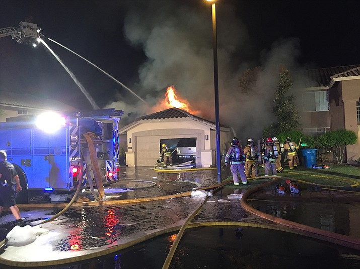 Firefighters extinguish flames caused by a plane crashing into a home in Gilbert, Ariz., on Saturday, Sept. 17, 2016. Federal investigators are trying to determine what led the plane carrying several skydivers to crash. The pilot and four skydivers were able to parachute out.