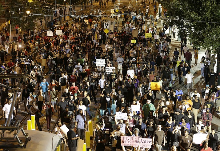 Demonstrators protest Tuesday's fatal police shooting of Keith Lamont Scott in Charlotte, N.C. on Wednesday, Sept. 21, 2016. Protesters rushed police in riot gear at a downtown Charlotte hotel and officers have fired tear gas to disperse the crowd. At least one person was injured in the confrontation, though it wasn't immediately clear how. Firefighters rushed in to pull the man to a waiting ambulance.