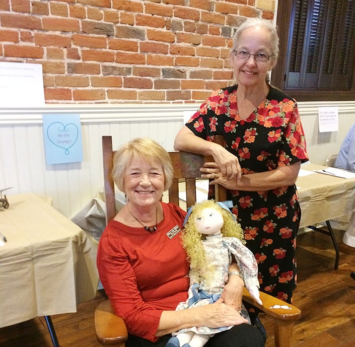 Coalition for Compassion and Justice Board President Mary Lea Adkins sits in a chair embellished with hand paintings by CCJ founder and Director of Special Programs Diane Iverson (behind) holding a handmade doll donated to the auction.