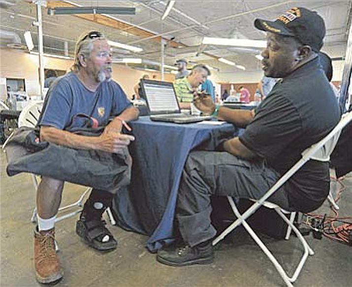 Anthony Irby with the Phoenix VA Homeless Veteran Outreach Program talks with Navy Veteran Don Rockwood about correcting his VA benefits during the 2015 Homeless Veteran Stand Down event at Frontier Village in Prescott.