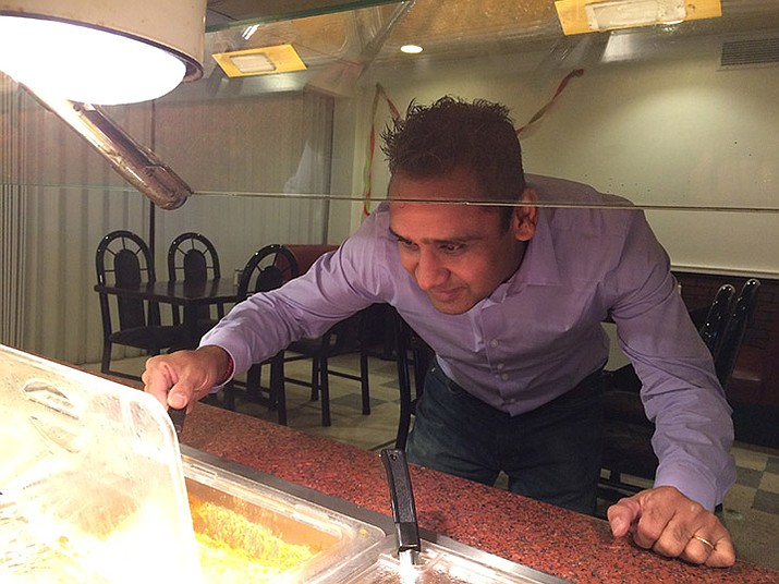 Neel Patel, owner of India Spice-N-Bar restaurant that opened Sept. 5, checks on some of his food dishes after a busy lunch hour.