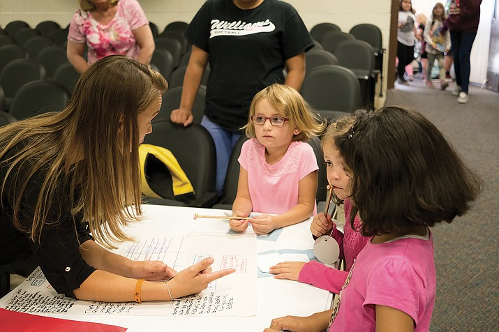 Williams Elementary-Middle School language arts teacher Lela Schober talks to first grader Vetta Martinez and other students as her eighth grade class teaches them about the Olympics during a special presentation Aug. 23.
