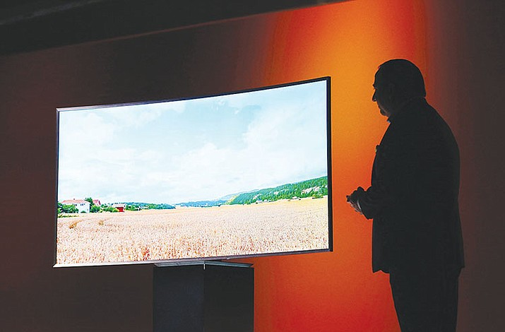 Joe Stinziano, executive vice president of Samsung Electronics America, introduces a Samsung SUHD 4K TV at a news conference in Las Vegas. An environmental group is accusing a trio of major TV makers of engineering their sets to make them look more energy efficient than they actually are.