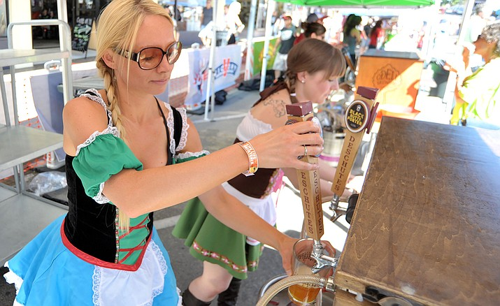 Kate Hope, left, and Katie Knapp pour a couple of beers for waiting patrons during the 2015 Prescott Oktoberfest in downtown Prescott. This year's event spans two days, Sept. 24-25.