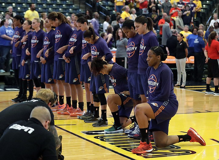 Kelsey Bone of the Phoenix Mercury, right, and Mistie Bass, second from right, kneel during the playing of the national anthem before the start of a first round WNBA playoff game Sept. 21.
