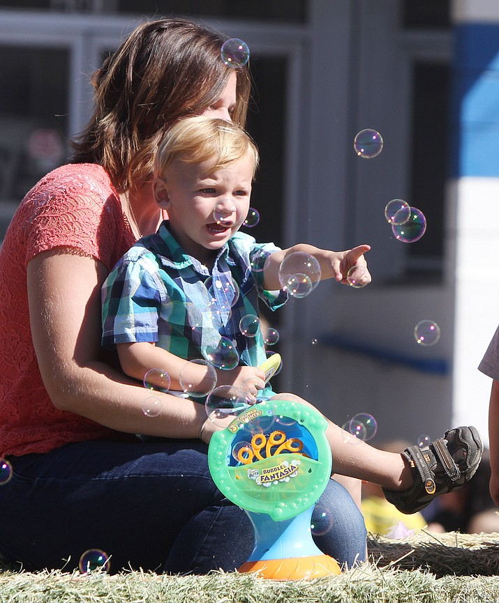 Briannah Poston, 4, doesn't let the bubbles she's blowing distract her from something more interesting at Saturday's Andy Devine Days Parade.
