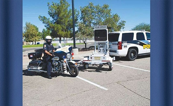 A motorcycle policeman sits behind the KPD's radar speed signs.