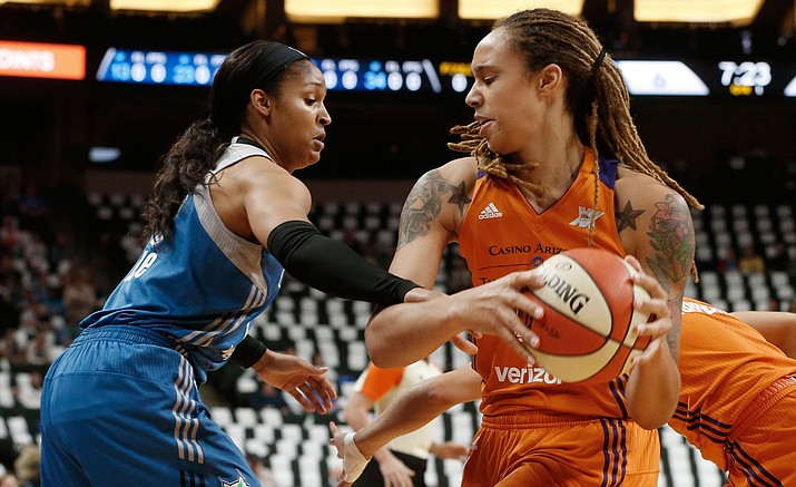 Phoenix Mercury's Brittney Griner, right, keeps the ball away as Minnesota Lynx's Maya Moore defends in the first quarter of a WNBA playoff semi-finals basketball game Wednesday, Sept. 28, in St. Paul, Minn.