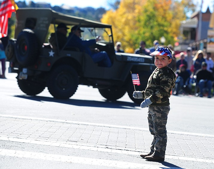 Gunner Hoover, who's father is a U.S. Marine, waves his flag during the 2015 Veteran's Day Parade through downtown Prescott.