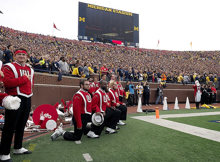 Four members of the Wisconsin Marching Band take a knee on the sidelines during the playing of the national anthem before an NCAA college football game at Michigan Stadium in Ann Arbor, Mich., Saturday.