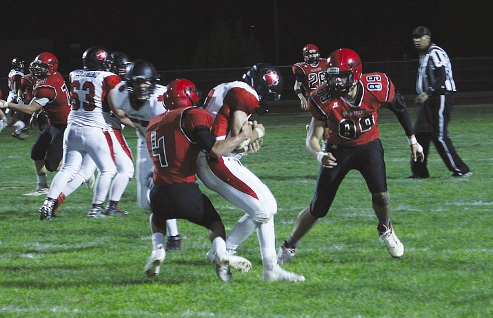 Lee Williams' Tyler Miner (4) puts the exclamation point on the Volunteers' 21-6 Homecoming Game win over Coconino with a sack late in the fourth quarter Friday at LWHS. The Vols' Marco Narvarte (89) closes in.