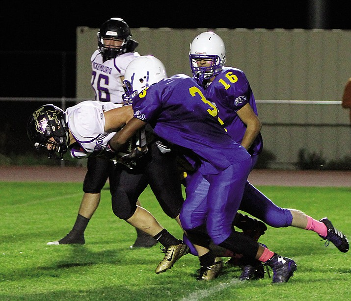 Kingman's Damon Heidorf (3) got his hands on this Wrangler ball carrier, but that didn't happen much in Wickenburg's 53-6 win over Kingman on Friday at KHS.