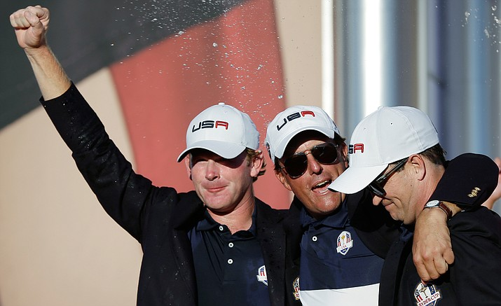 United States' Brandt Snedeker, Phil Mickelson and Dustin Johnson celebrate during the closing ceremony of the Ryder Cup golf tournament Sunday, Oct. 2, at Hazeltine National Golf Club in Chaska, Minn.
