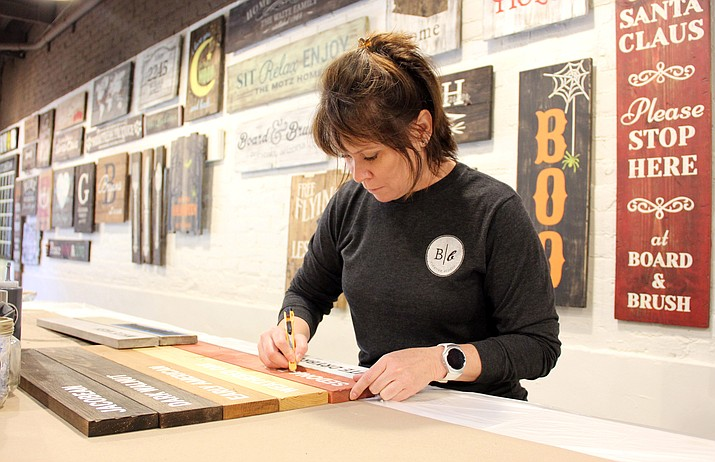 Crista Toth puts some finishing touches on some signs she intends to hang inside her new small business, Board & Brush Creative Studio.