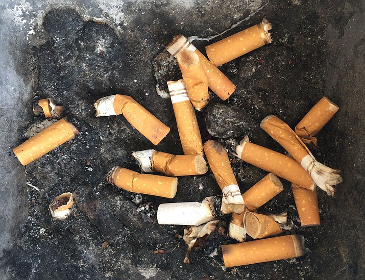 An ashtray in the Kingman Square Shopping Center is filled with cigarette butts. The Centers for Disease Control and Prevention reported that adult smoking in Arizona has dropped to 14 percent from 19 percent in 2011.