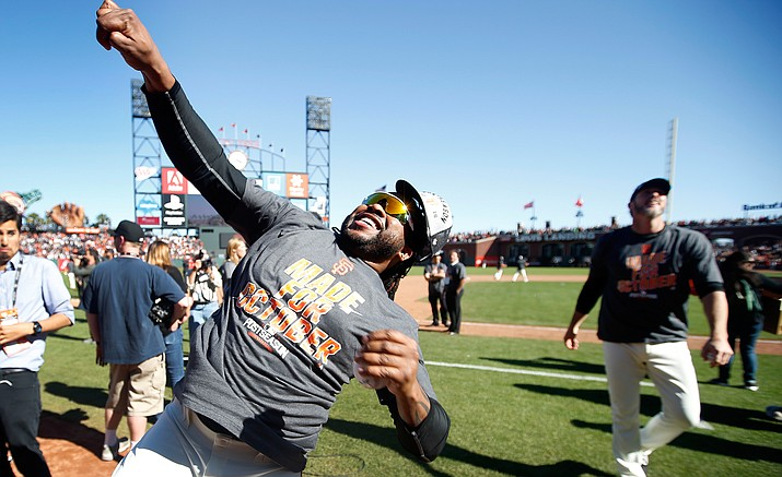 San Francisco Giants' Johnny Cueto, throws a ball into the crowd during a celebration on the field after clinching NL second-place wild card spot following their win over the Los Angeles Dodgers in a baseball game in San Francisco, Sunday, Oct. 2.